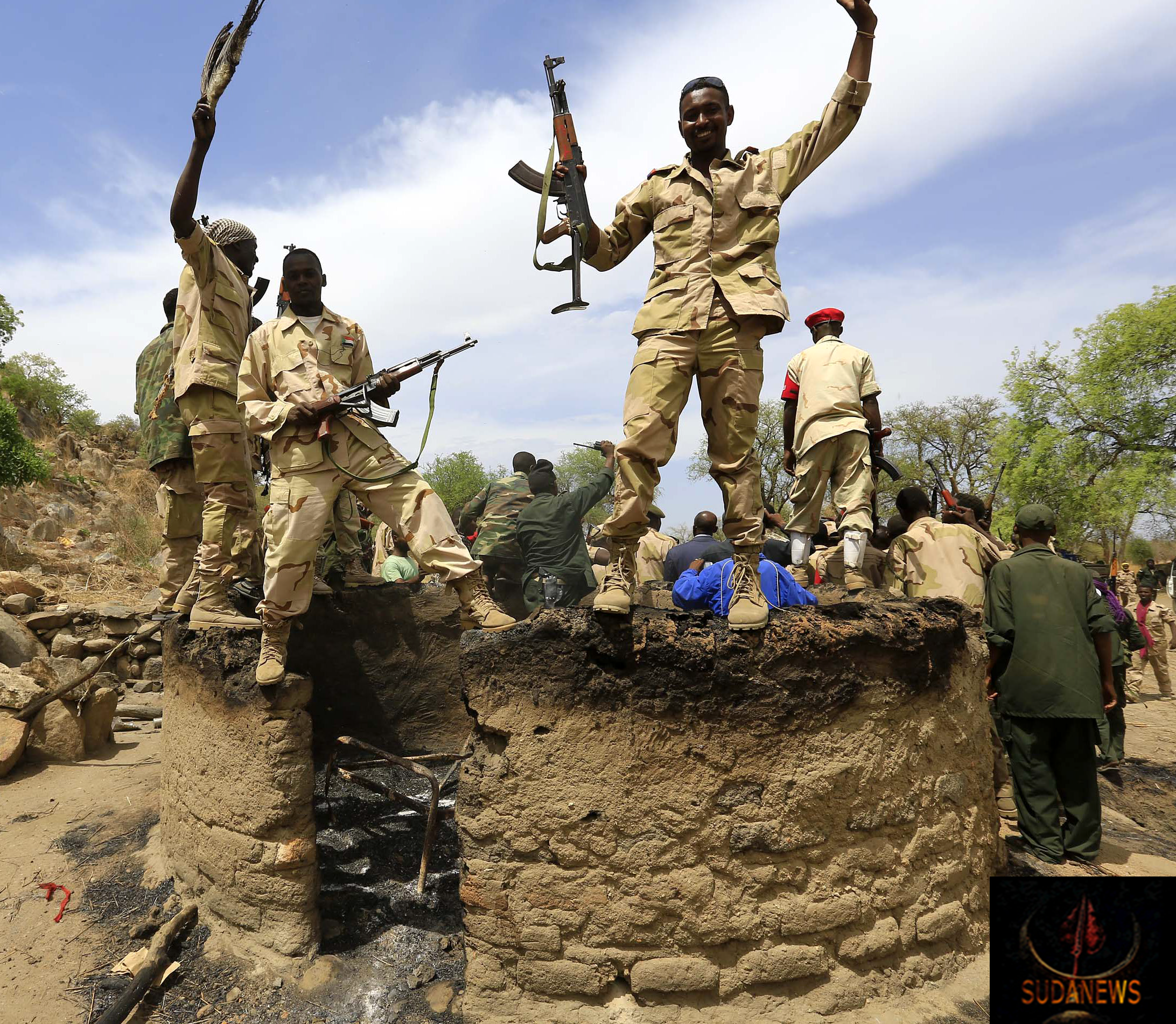 Members of the Rapid Support Forces celebrate their victory for the cameras while perched atop a burned dwelling in Sudan's South Kordofan state on May 20, 2014. STR/AFP/GETTY IMAGES